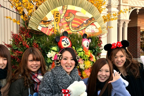"Young Japanese women pose in front of a New Year's decorations with picture of a snake to mark the Year of the Snake in the Chinese zodiac, on display at Tokyo Disneyland in Urayasu, suburban Tokyo on January 1, 2013. Thousands of people visited the theme park to mark the start of the New Year's holiday, the biggest one of the year in Japan. The ""Year of the Snake"" will be marked across much of the rest of East and Southeast Asia in mid-February, 2013 at the Lunar New Year holidays.    AFP PHOTO / Yoshikazu TSUNO"