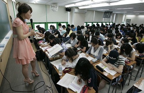 "English teacher Rose Lee gives a lecture at a cram school in Seoul June 18, 2009. In her miniskirt, boots and fashionable tops, Lee looks more like a university student, but she's actually one of the country's highest paid English teachers. Calling herself the ""Queen of English"" but who asked to be interviewed in Korean, Lee expects to make more than $7 million a year mostly through online classes. Picture taken June 18, 2009.     REUTERS/Lee Jae-Won (SOUTH KOREA EDUCATION BUSINESS SOCIETY)"