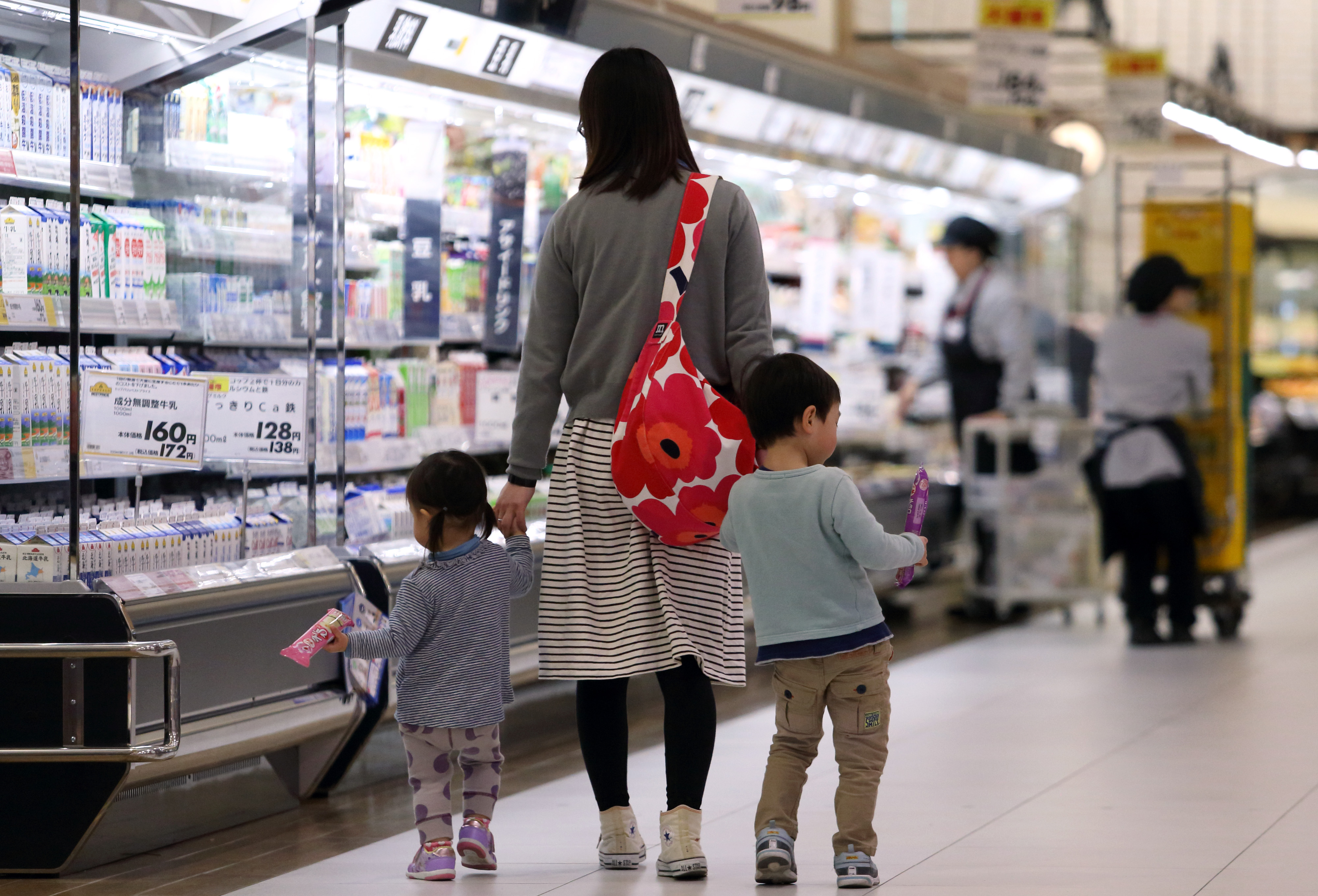 A mother and her children walk through an Aeon Co. supermarket in Chiba, Japan, on Tuesday, April 1, 2014. Japan's economy will probably withstand a sales tax increase that takes effect today as Prime Minister Shinzo Abe prepares economic stimulus measures and companies raise wages, the country's new bank lobby chief Nobuyuki Hirano said. Photographer: Tomohiro Ohsumi/Bloomberg