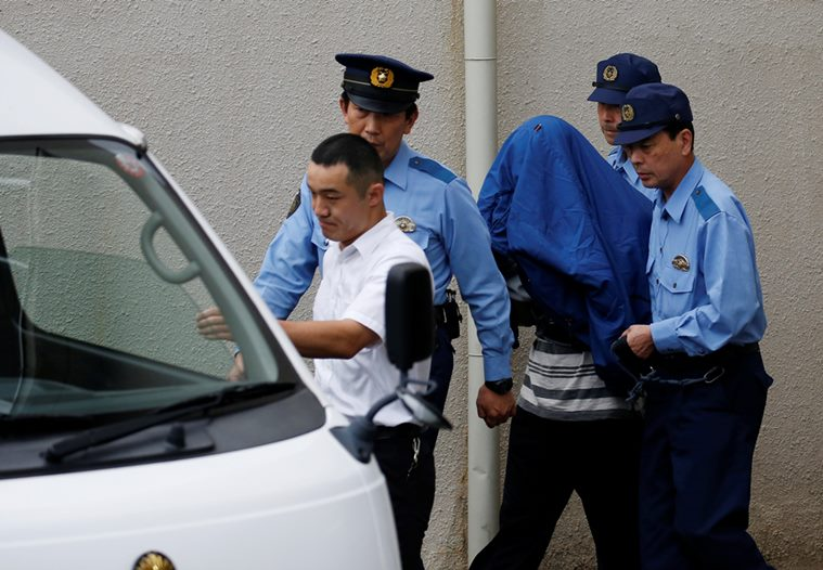 Satoshi Uematsu (C, with a jacket over his head), suspected of a deadly attack at a facility for the disabled, is escorted by police officers as he is taken from local jail to prosecutors, at Tsukui police station in Sagamihara, Kanagawa prefecture, Japan, July 27, 2016. REUTERS/Issei Kato