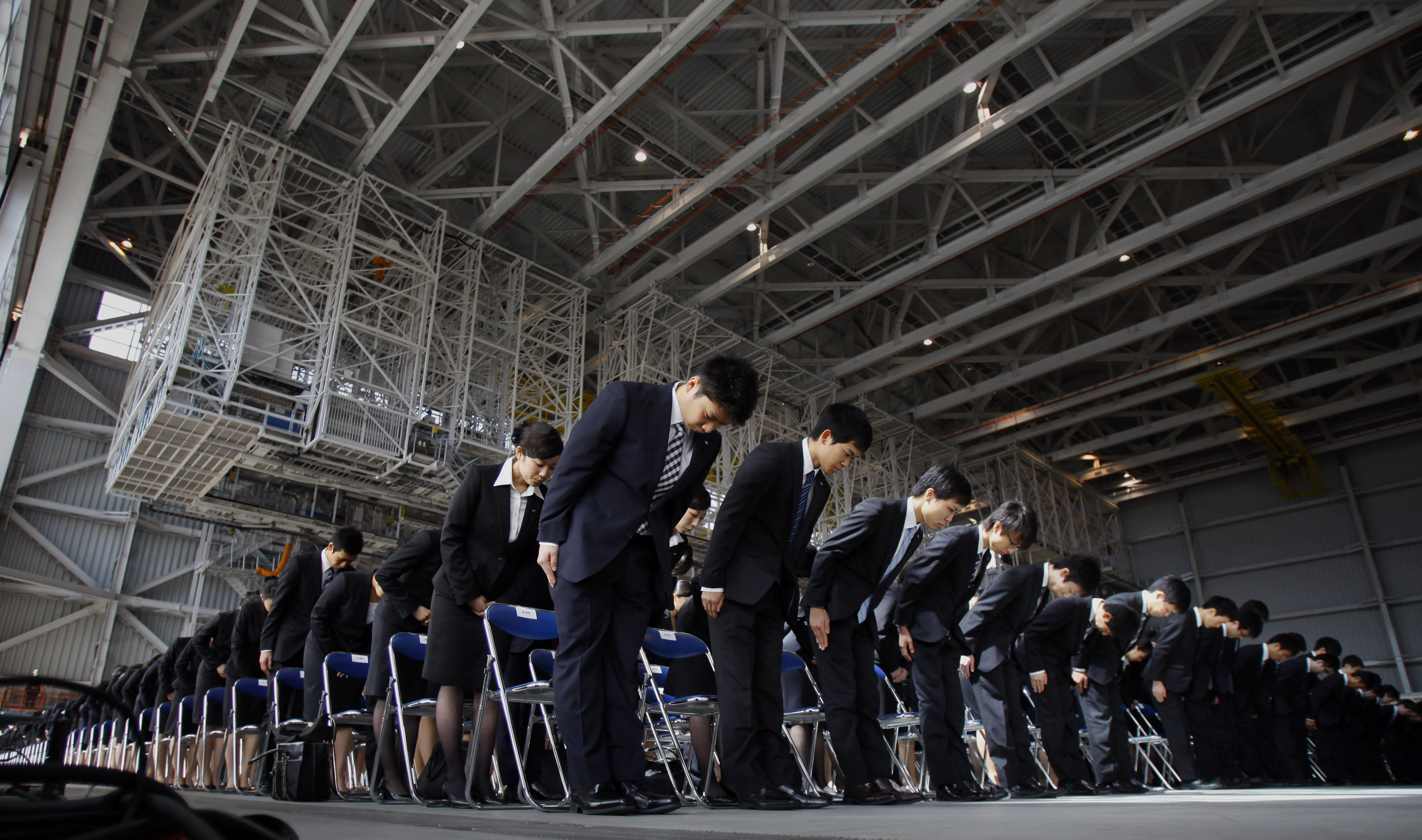 Newly hired employees of All Nippon Airways and ANA group companies bow during an initiation ceremony at the company's aircraft maintenance hangar in Haneda airport in Tokyo Monday, April 1, 2013. A total 1,068 new recruits attended the ceremony, according to the company. (AP Photo/Junji Kurokawa)